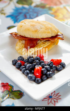 A bacon, egg and cheese breakfast sandwich with a side of berries. - Stock Photo