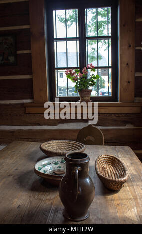 Room on the old weekend cottage. In the middle there is an oak table. On the table there is shallow flasket,  jug, bowl and a wooden spoon. There is a - Stock Photo