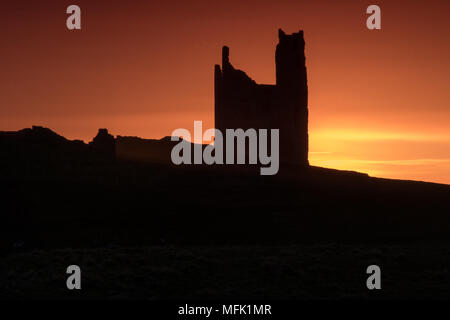 Dunstanburgh Castle, Northumberland. 26th April 2018. The sun rises behind Dunstanburgh castle on a Cloudy day.  Credit: Dan Cooke Credit: Dan Cooke/Alamy Live News - Stock Photo