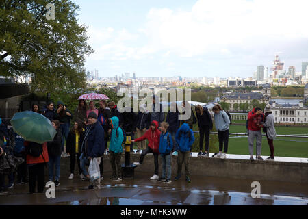 London,UK,26th April 2018,Heavy rainfall in Greenwich Park, London. People use umbrellas as they take photos of the view across London.Credit Keith Larby/Alamy Live News - Stock Photo