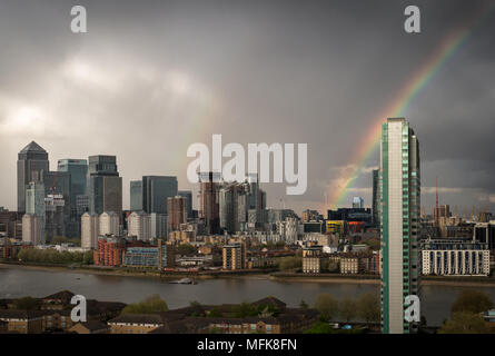 London, UK. 26th April, 2018. UK Weather: A rainbow breaks over east London including Canary Wharf business park buildings during a brief afternoon rainstorm. © Guy Corbishley/Alamy Live News - Stock Photo