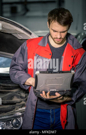 mechanic using special laptop computer to check car engine - Stock Photo