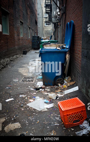 Large, overflowing garbage cans in a back alley in Pittsburgh, Pennsylvania, USA - Stock Photo