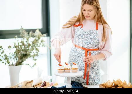 Half-size portrait of a beautiful female decorating freshly baked cupcakes and smiling. - Stock Photo