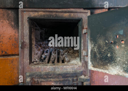 Rural stove with open door. Lot of ashes and charcoal visible inside the stove - Stock Photo