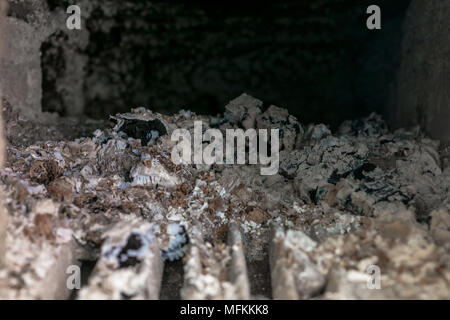 View of inside rural stove with a lot of ashes and charcoal - Stock Photo