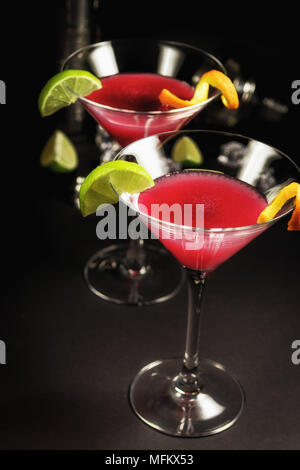 Alcohol drink cocktail Cosmopolitan with lime on black background - Stock Photo