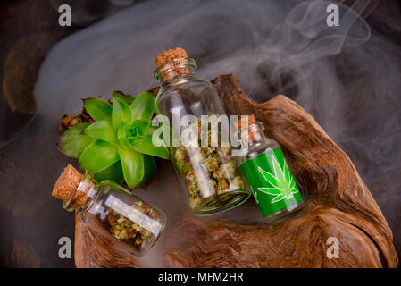 Assorted jars with cannabis calyxes (sour tangie strain) isolated on black background - Medical marijuana dispensary concept - Stock Photo
