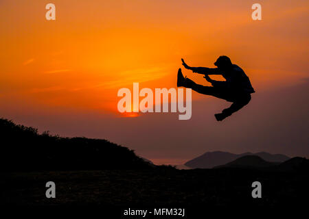 silhouette of young man jumping with twilight sky. - Stock Photo