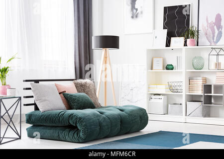 ... Cushions on green futon in modern bedroom interior with black wooden l& and posters - Stock & Emerald futon with pillows in a modern living room interior with ...