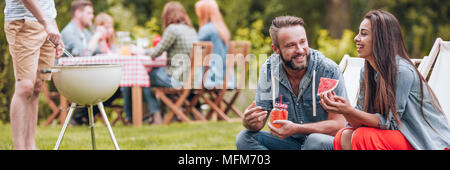 Smiling woman eating watermelon and her  friend drinking juice during garden party - Stock Photo