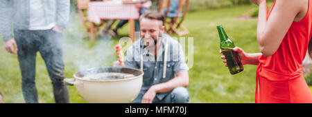 Panorama of woman in red dress drinking beer during a garden party - Stock Photo