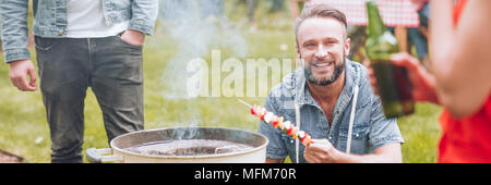 Smiling man grilling shashlik during barbeque party with friends - Stock Photo