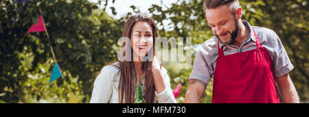 Friends having fun while grilling in the garden in the summer - Stock Photo
