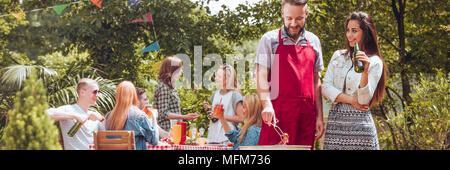 Smiling woman drinking beer and her friend grilling food during a meeting outside - Stock Photo