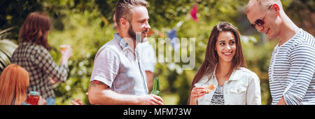 Panorama of friends enjoying time together while drinking beer during outdoor party - Stock Photo