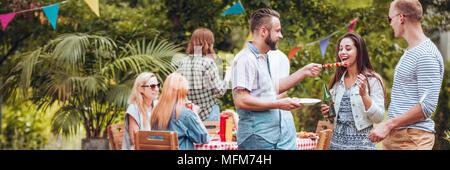 Group of friends having fun while eating grilled food and drinking beer during an outdoor party - Stock Photo