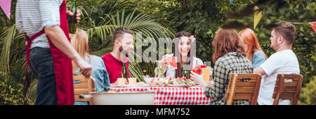 Panorama of smiling friends enjoying a birthday party in the garden - Stock Photo
