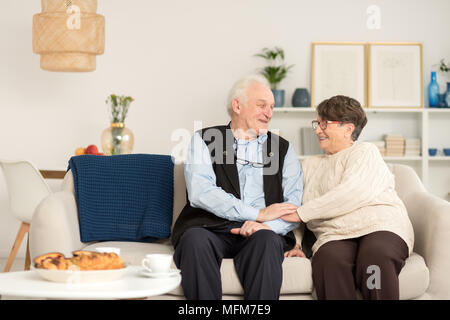 Happy senior couple in love showing tenderness and enjoying their time together holding hands and sitting on sofa with blue blanket in a cozy living r - Stock Photo