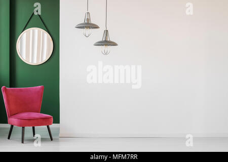 Minimalist living room interior with white, empty wall, comfortable retro chair and a round hanging mirror in green corner - Stock Photo