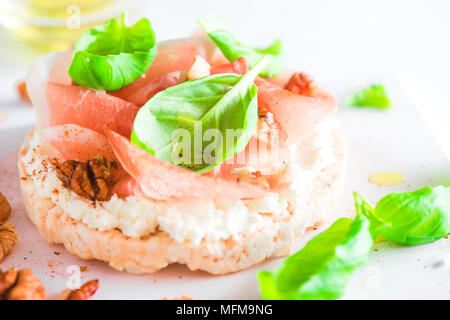 Crisp bread healthy snack with Parma ham, soft cottage cheese, walnuts, olive oil, paprika, fresh basil leaves. Easy breakfast close-up on a white bac - Stock Photo