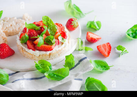 Healthy snack with crisp bread, fresh strawberries, goat cheese, and basil leaves. Easy breakfast close-up on a white background with copy space. - Stock Photo