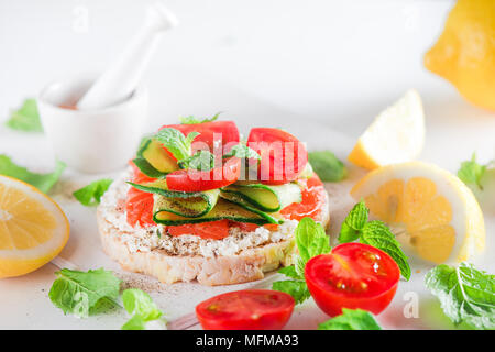 Crisp bread healthy snack with salmon, cottage cheese, cucumber stripes, fresh cherry tomatoes, mint, lemon juice, pepper. Easy breakfast close-up on  - Stock Photo