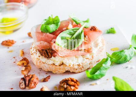 Crisp bread healthy snack with Parma ham, soft creme cheese, olive oil, fresh basil leaves, walnuts. Easy breakfast close-up on a white background wit - Stock Photo