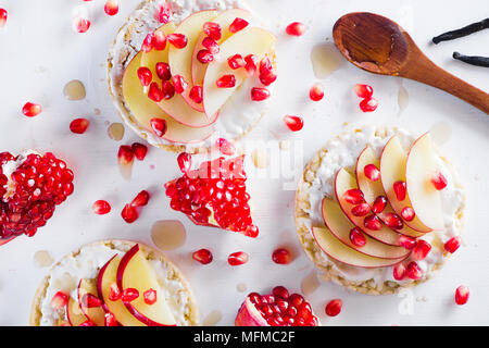 Crisp bread healthy snack with apple slices, soft cottage cheese, vanilla, honey, pomegranate seeds. Easy breakfast concept on a white background with - Stock Photo