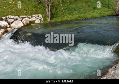 A close up photograph of a small waterfall made from stone wall, Small waterfall. The height difference of the water flow in the river is equipped - Stock Photo
