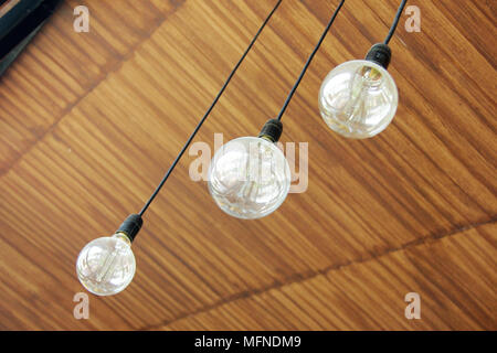 Three retro light bulbs hanging from wood ceiling in coffee shop - Stock Photo