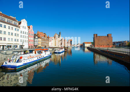 Early morning reflections and historic architecture, Motlawa river, Gdansk, Poland. A barge waits at the dockside. Colourful scene with deep blue sky - Stock Photo