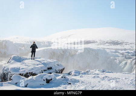 Panoramic snow scene.. Girl watching incredible falls at Godafoss  on the Skjalfandafljot river, Iceland. Snowy winter landscape, with blue sky - Stock Photo