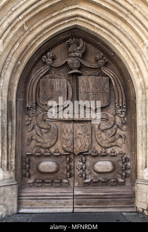 Old wooden door with carving, entrance of Abbey Church of St.Peter and St.Paul, commonly known as Bath Abbey. Anglican parish church and former Benedi - Stock Photo