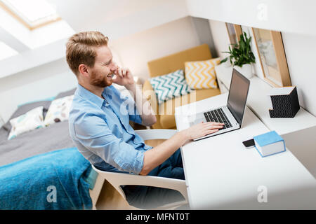 Self employed businessman working from home - Stock Photo