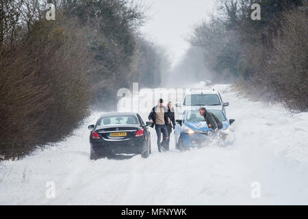 A man using a spade to dig his car out of a snow drift standing in deep snow he has to battle the strong winds gusting across the country road as other vehicles pass by. - Stock Photo
