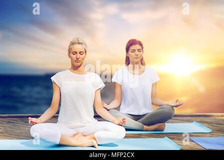 women meditating in yoga lotus pose outdoors - Stock Photo