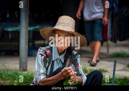 Fuli Village, Yangshuo, Guangxi, China - August 2, 2012: Portrait of an old chinese woman selling vegetables in a street market at the Fuli Village in - Stock Photo