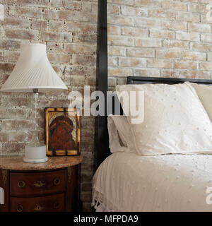 Lamp next to dark wood four poster bed in country style bedroom - Stock Photo