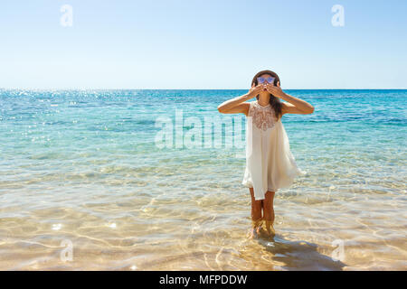 girl sends an air kiss to the camera. a beautiful carefree Woman relaxing at the beach enjoying her sun white dress. - Stock Photo
