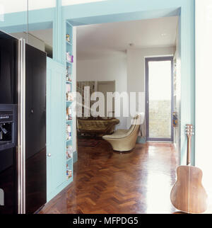 Kitchen with wooden flooring, leading into a sitting room area. - Stock Photo
