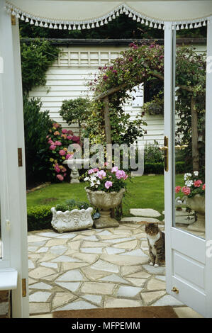View through doorway to garden with a patio in front of a small lawn with stone plant pots. - Stock Photo