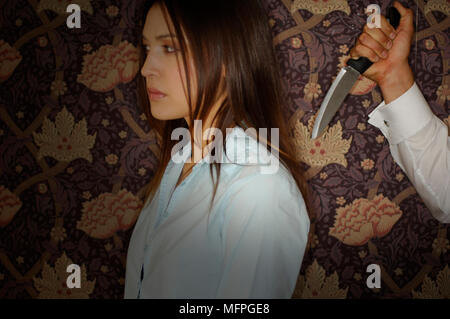 Close-up of a man's hand holding a knife behind a businesswoman's back   Ref: CRUSC 10016 090  Compulsory Credit: Stuart Cox/Photoshot - Stock Photo