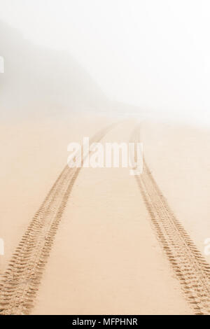 Road on sand goes to fog vertical photo - Stock Photo