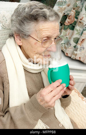 Elderly woman using a steam inhaler inhaling a decongestant for colds & bronchitis model release - Stock Photo