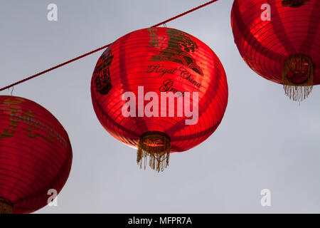 Red lanterns hang above the street, strung between buildings, in London UK's Chinatown district in celebration of Chinese New Year - Stock Photo