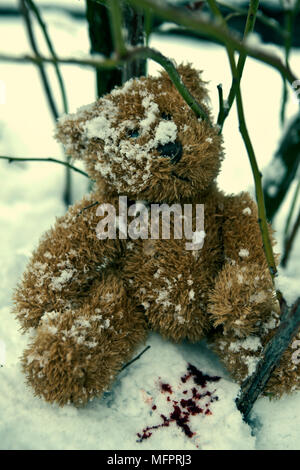 a forgotten teddy bear in the snow with blood drops - Stock Photo