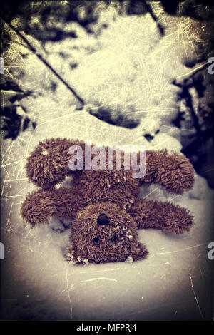 a forgotten teddy bear in the snow - Stock Photo
