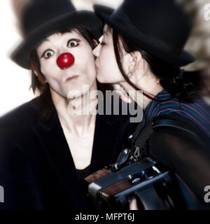 a couple of clowns - the woman kisses the man - Stock Photo