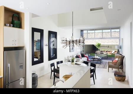 Modern open plan room with kitchen dining and sitting areas and open patio doors - Stock Photo